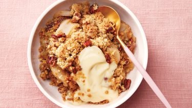 A bowl of apple crumble with a scoop of vanilla pudding on a light pink background