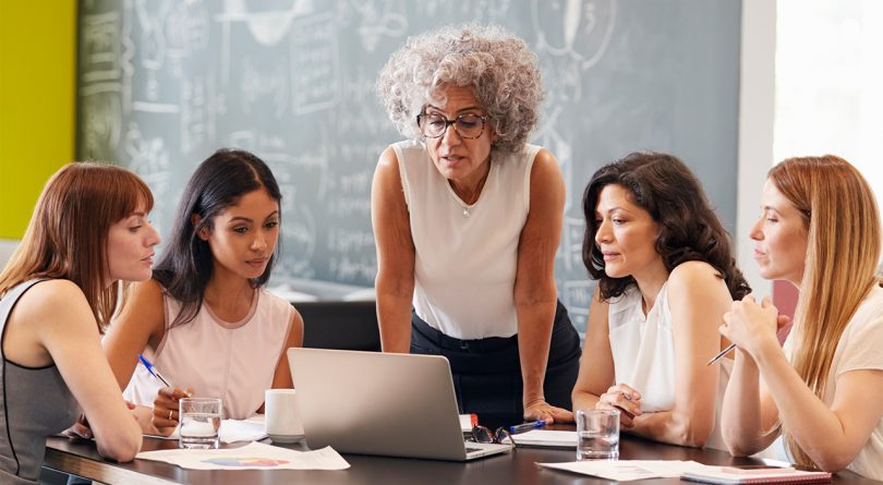 Five diverse business women gathered around a table with a laptop and papers on top of it at the office with a blackboard in the background