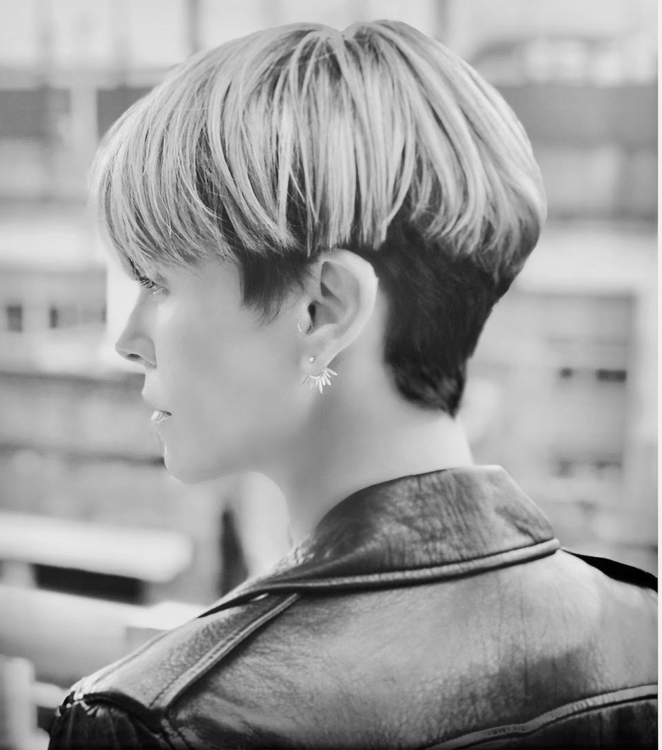A photo of Charlize Theron from the shoulders up. She's wearing a leather jacket and has a bowl cut with honey highlights and a dark undercut.