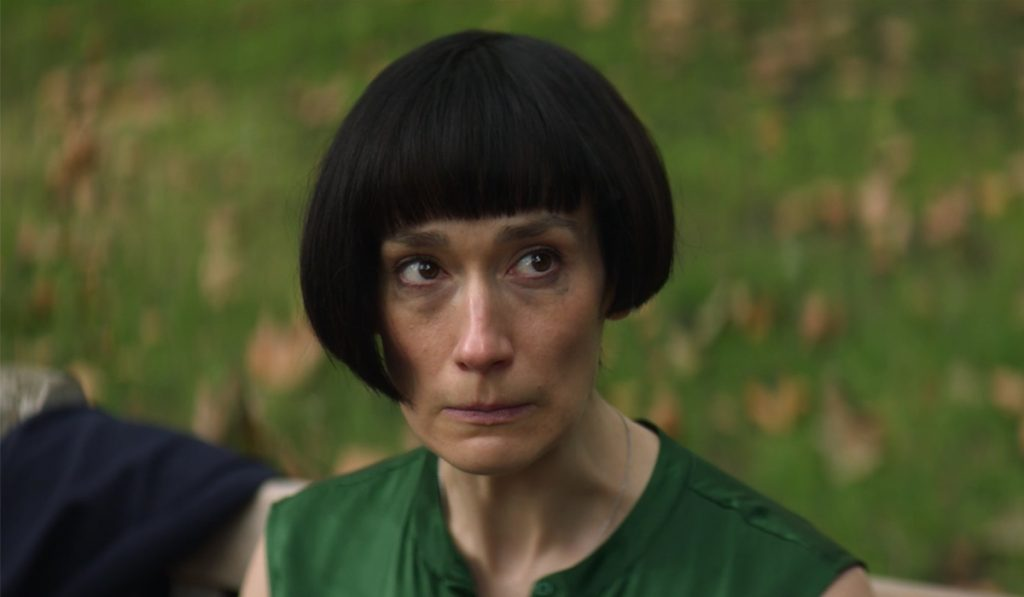 The character Claire from Fleabag is seen sitting on a park bench with a bowl cut.
