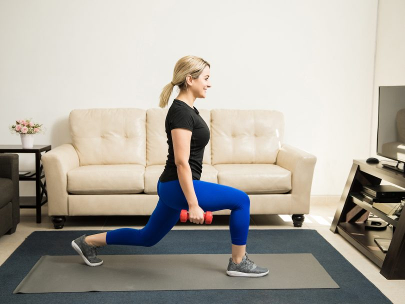 Profile view of a cute young woman doing couch exercises-kneeling lunges with dumbbells at home