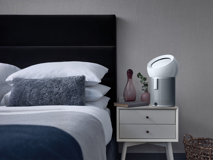 A Dyson Pure Cool Me personal purifying fan is on a nightstand on a bedroom decorated in cool, calming tones for a Dyson Pure Cool Me review and air purifier faq