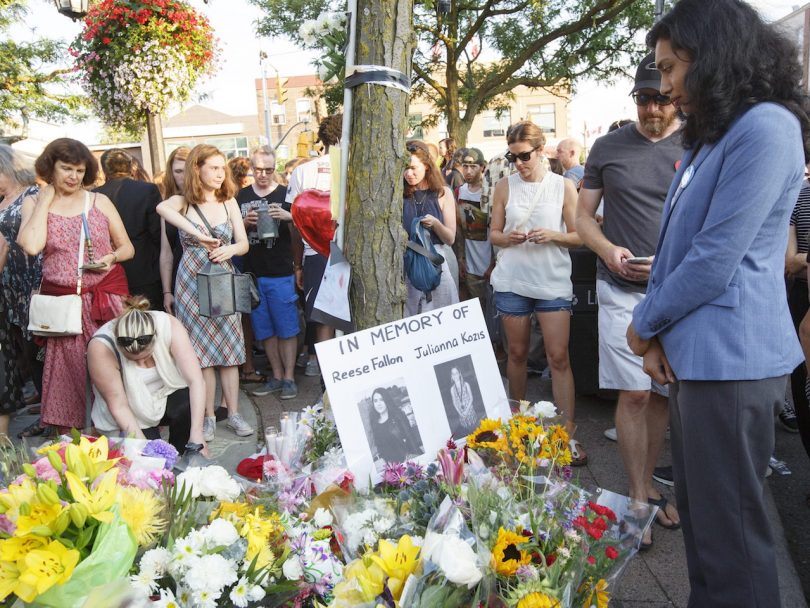 MPP Doly Becum, Scarborough South-West, leaves flowers by a poster of shooting victim Reese Fallon in Alexander the Great Parkette near Danforth Ave. in Greek Town in Toronto on July 25, 2018. The vigil honours the lives affected by the recent tragic shooting by a lone gunman who killed two young women and injured another thirteen people.