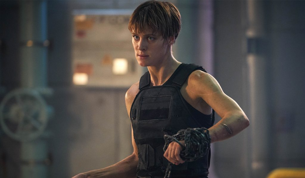 A still from the action movie Terminator: Dark Fate showing actress Mackenzie Davis wearing a bowl cut