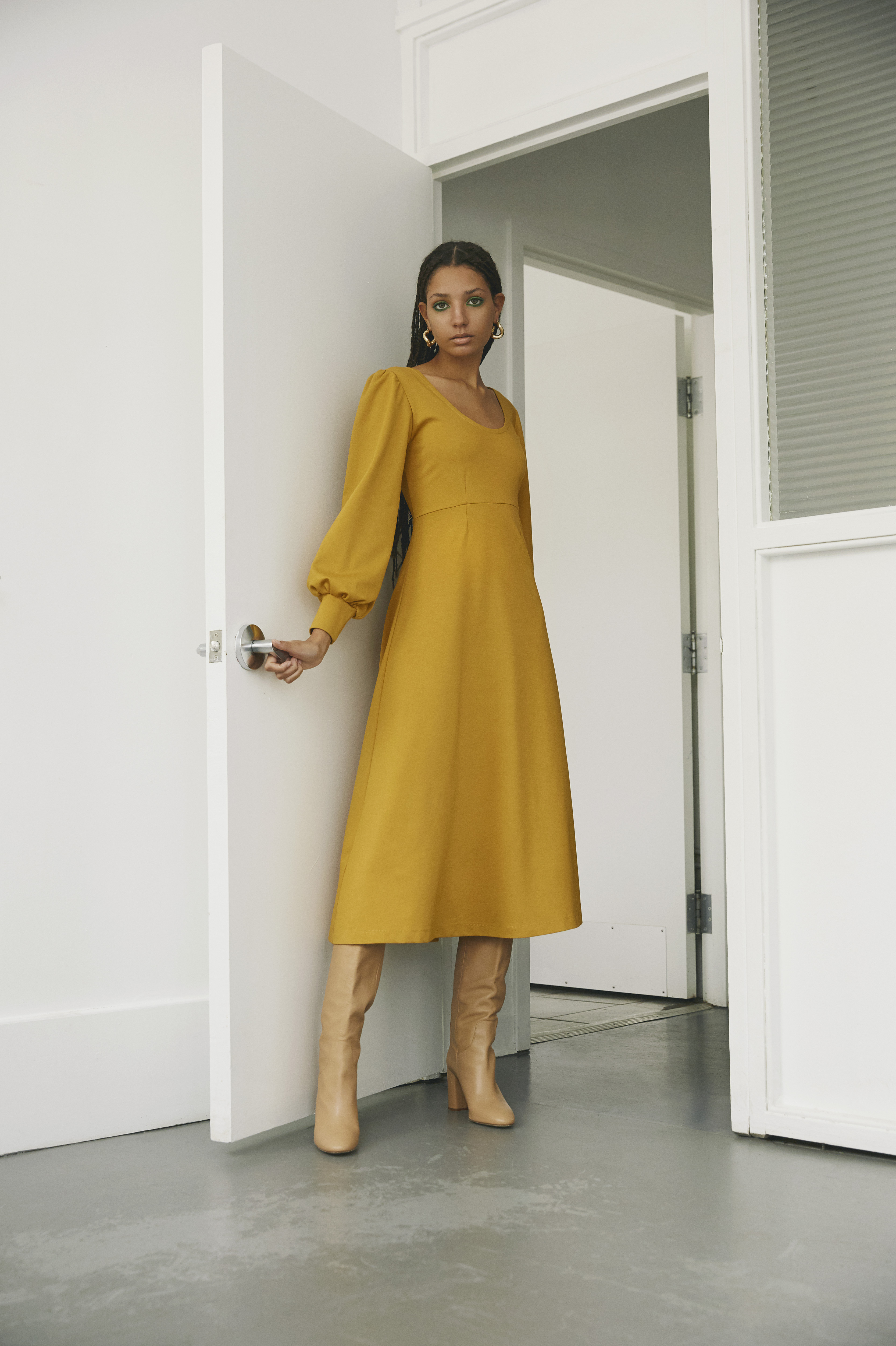 A model wears a calf-length mustard dress with balloon sleeves