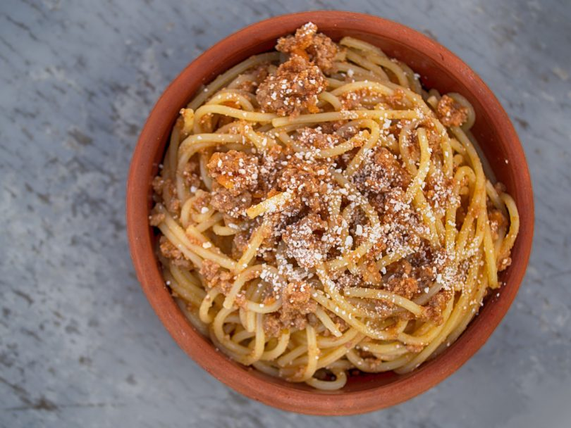 overhead shot of A red bowl holding spaghetti bolognese sitting on a grey background