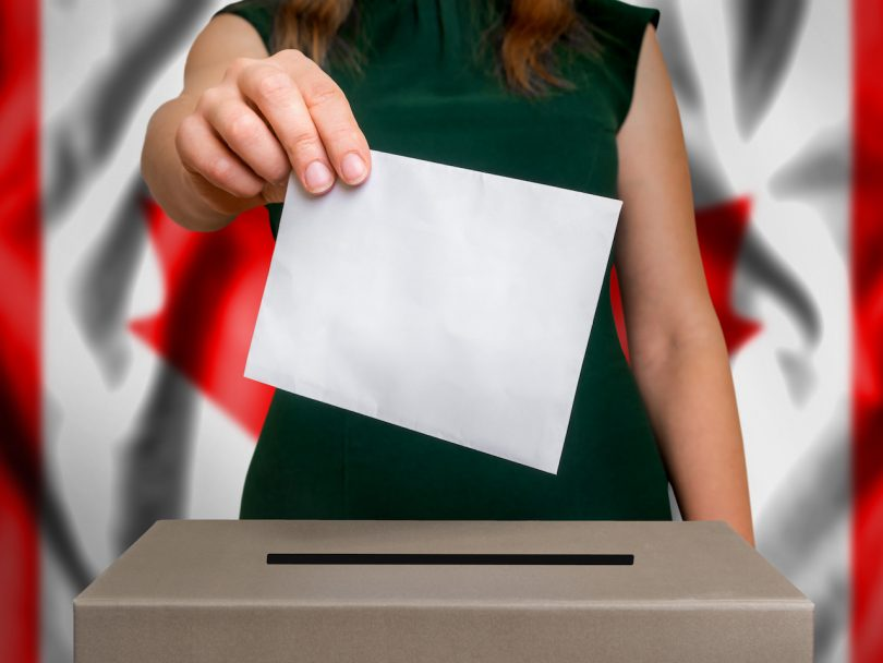 The hand of woman putting her vote in the ballot box. Flag of Canada on background.