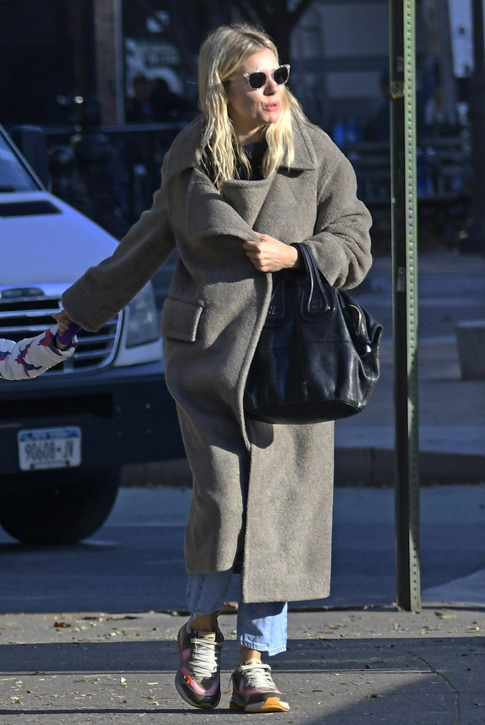 Sienna Miller walking in New York City wearing a greige Smythe teddy coat.