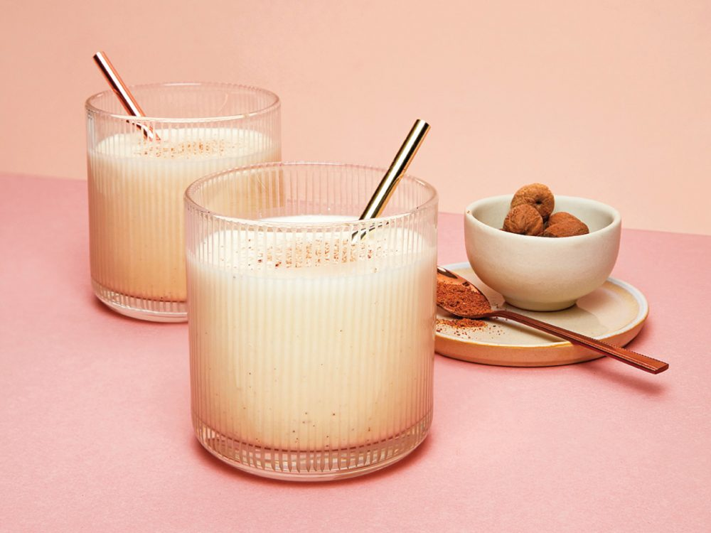 two tumblers of vegan eggnog garnished with cinnamon sticks sitting on a light pink background