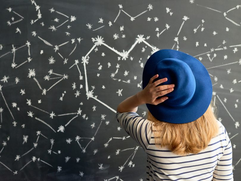 Rear view of young woman in striped shirt and hat looking at constellation in the shape of heart