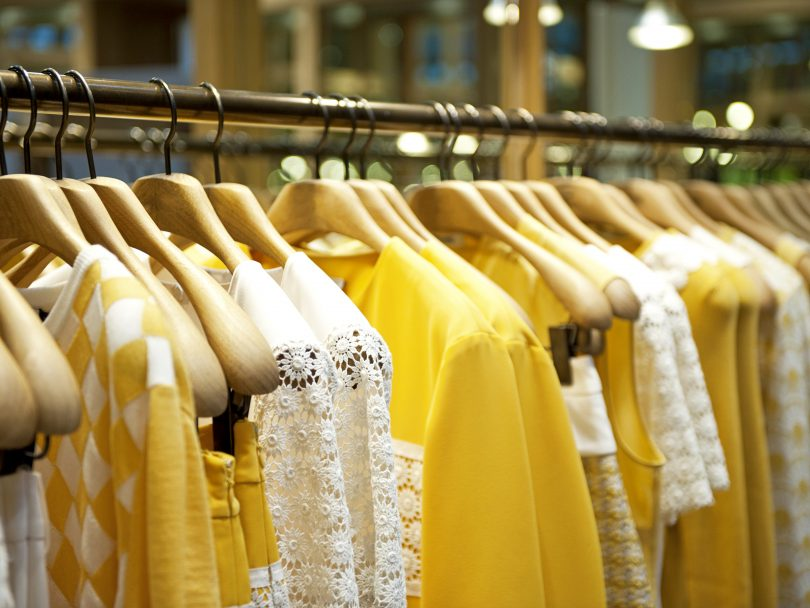 How to Buy Less Clothing: Yellow clothes on a rack