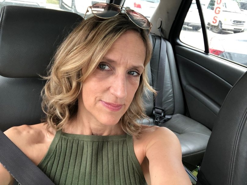 a woman takes a selfie wearing a green shirt in her car