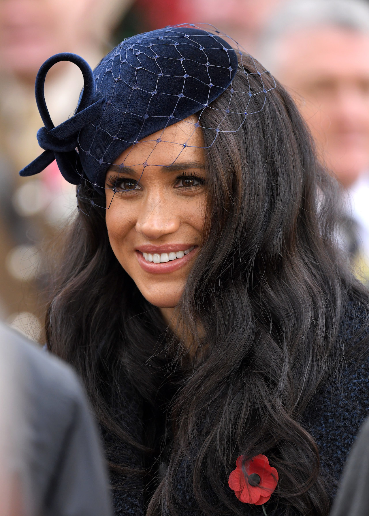 meghan markle with long brown hair wearing a navy blue hat