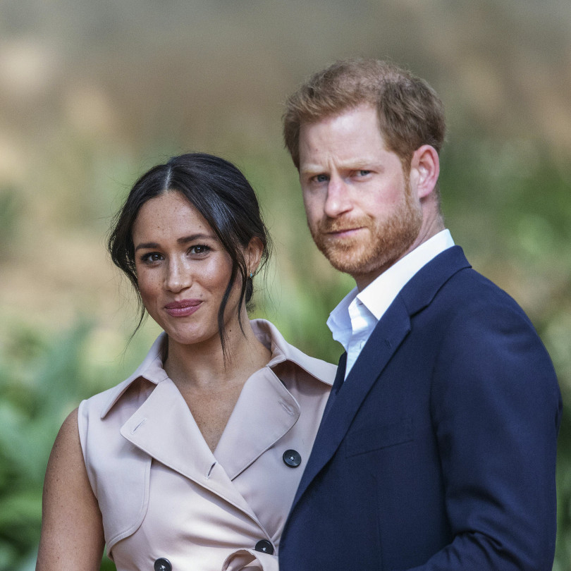 meghan markle wearing a pink shirt dress standing next to harry who is wearing a navy suit and white shirt