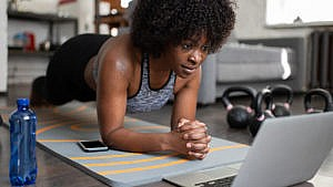 A woman does the plank exercise at home