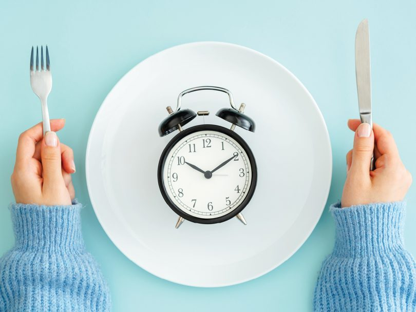 Intermittent Fasting feature image shows an overhead shot of an alarm clock resting face-up on a white plate with hands holding cutlery on either side of the plate