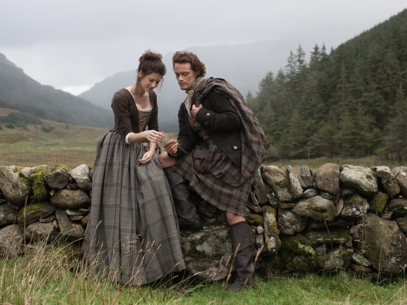 Outlander Reinvented My Sex Life-a man and a woman in 18th century Scotland sit on a stone wall close together