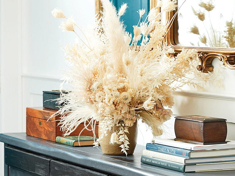 an organized hallway table with books and a vase of wild grass