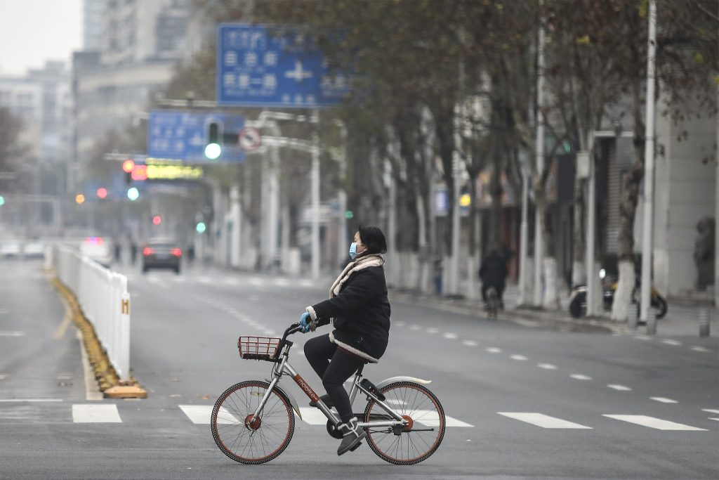 A woman wearing a protective mask rides a motorized bike on an empty road January 27, 2020 in Wuhan, China, where the new coronavirus is thought to have originated.