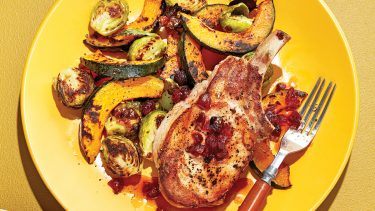 Pork chop, squash wedges and roasted brussels sprouts on light brown plate.