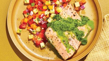 Trout with green sauce and pineapple-pepper salso on light brown plate.