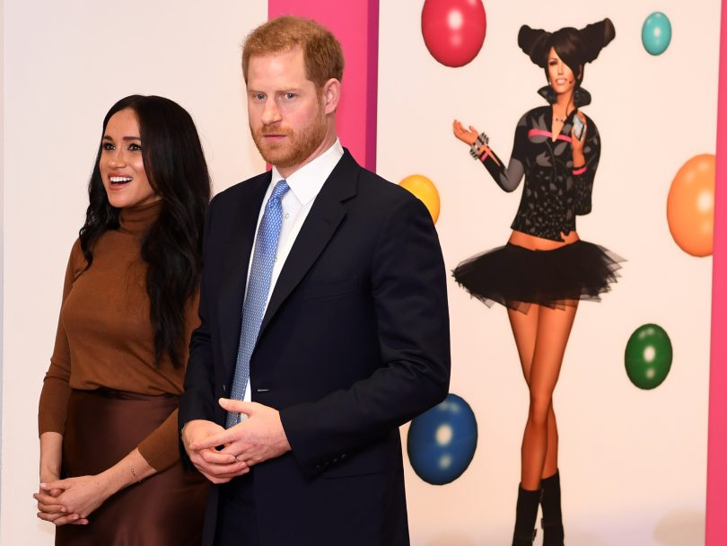 Prince Harry and Meghan Markle standing in front of art by Skawennati.