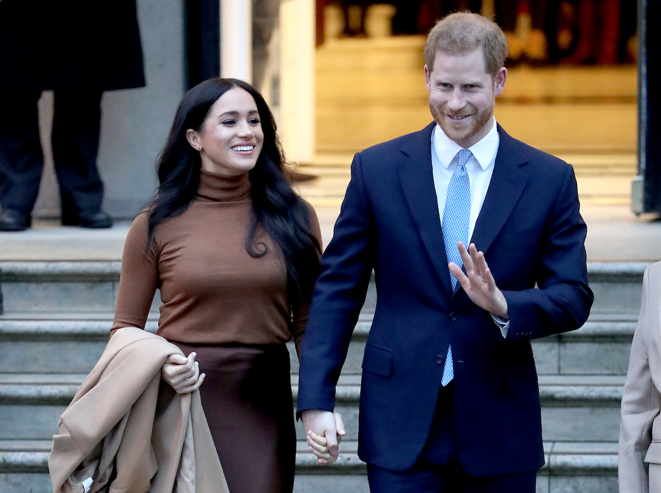 Meghan Markle Prince Harry ongoing discussions word Royal-meghan wearing a brown turtleneck and harry wearing a navy blue suit and light blue tie and white shirt walk hand-in-hand