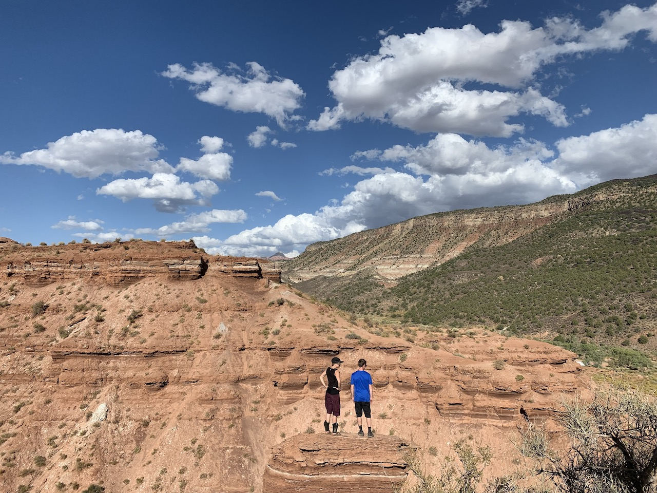 two small figures stand against a backdrop of blue skies, red cliffs and deep canyons