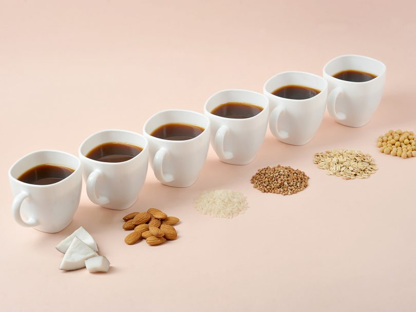 An array of coffee cups with plant-based milk ingredients.