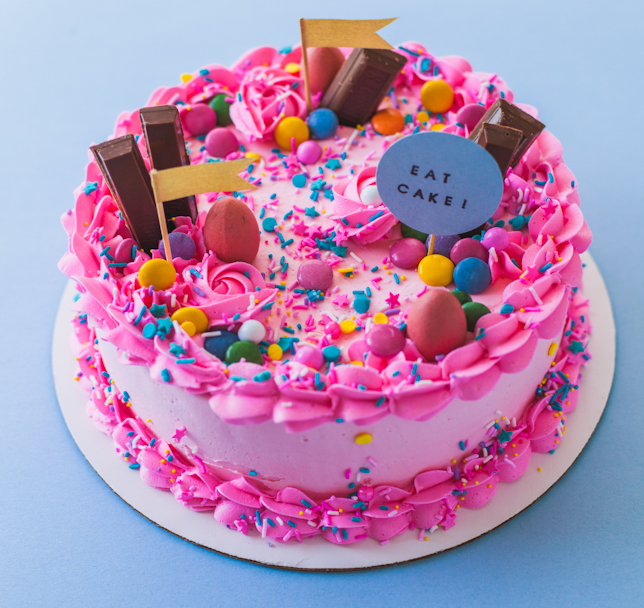 A pink cake covered in kit kats, chocolate eggs and sprinkles.