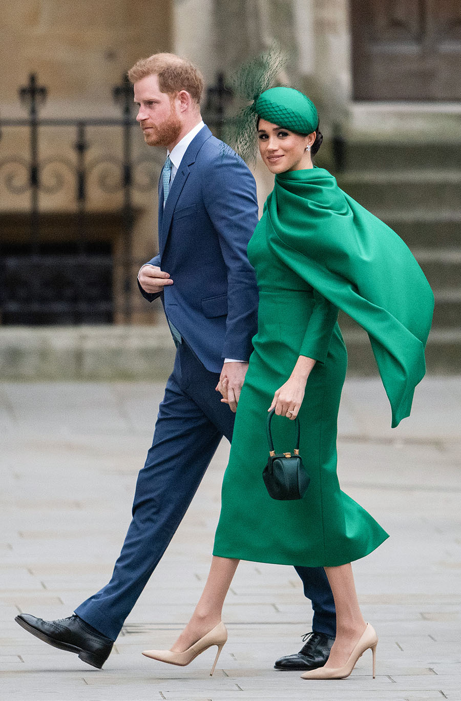 Meghan Markle and Prince Harry in a suit and a green dress walking into church