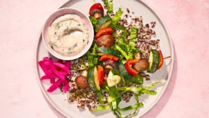 vegan vegetable kebabs with lemon-garlic sauce and quinoa on a neutral round plate