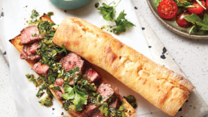 Steak sandwich with a tomato and arugula salad.