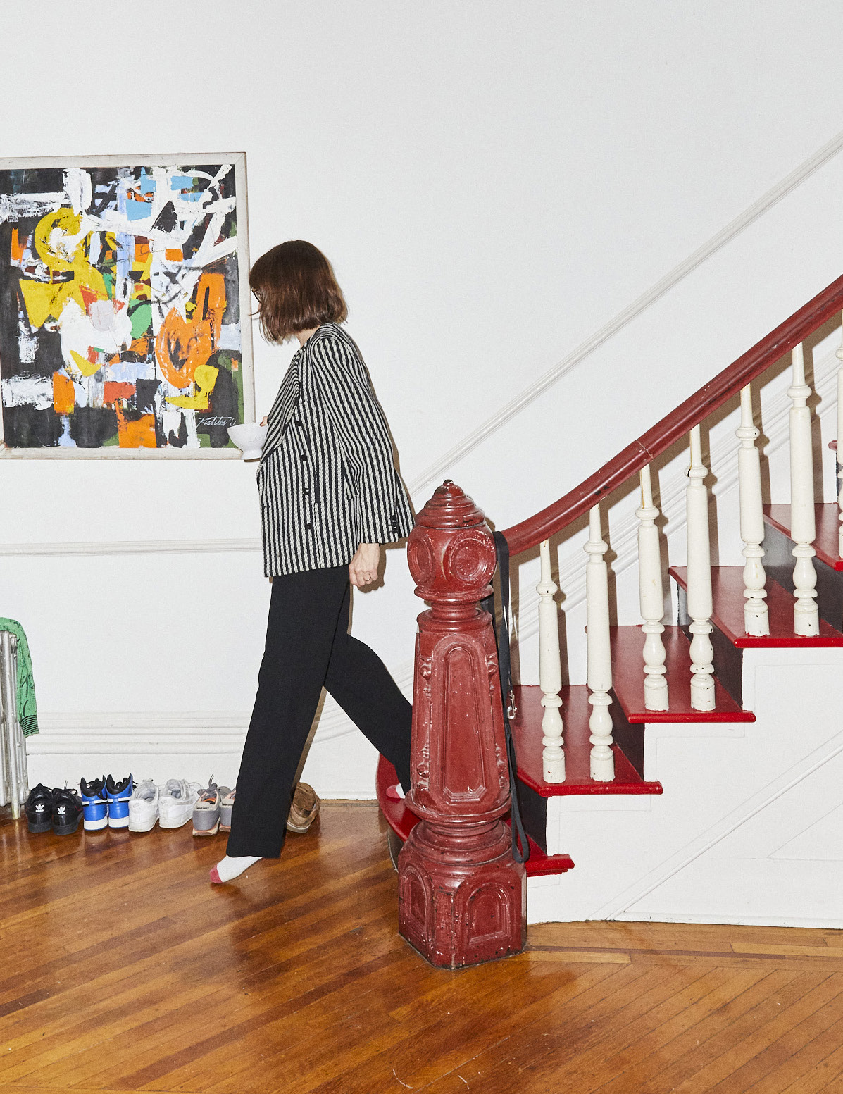 Dolly Wells walking down the stairs in her Brooklyn home.