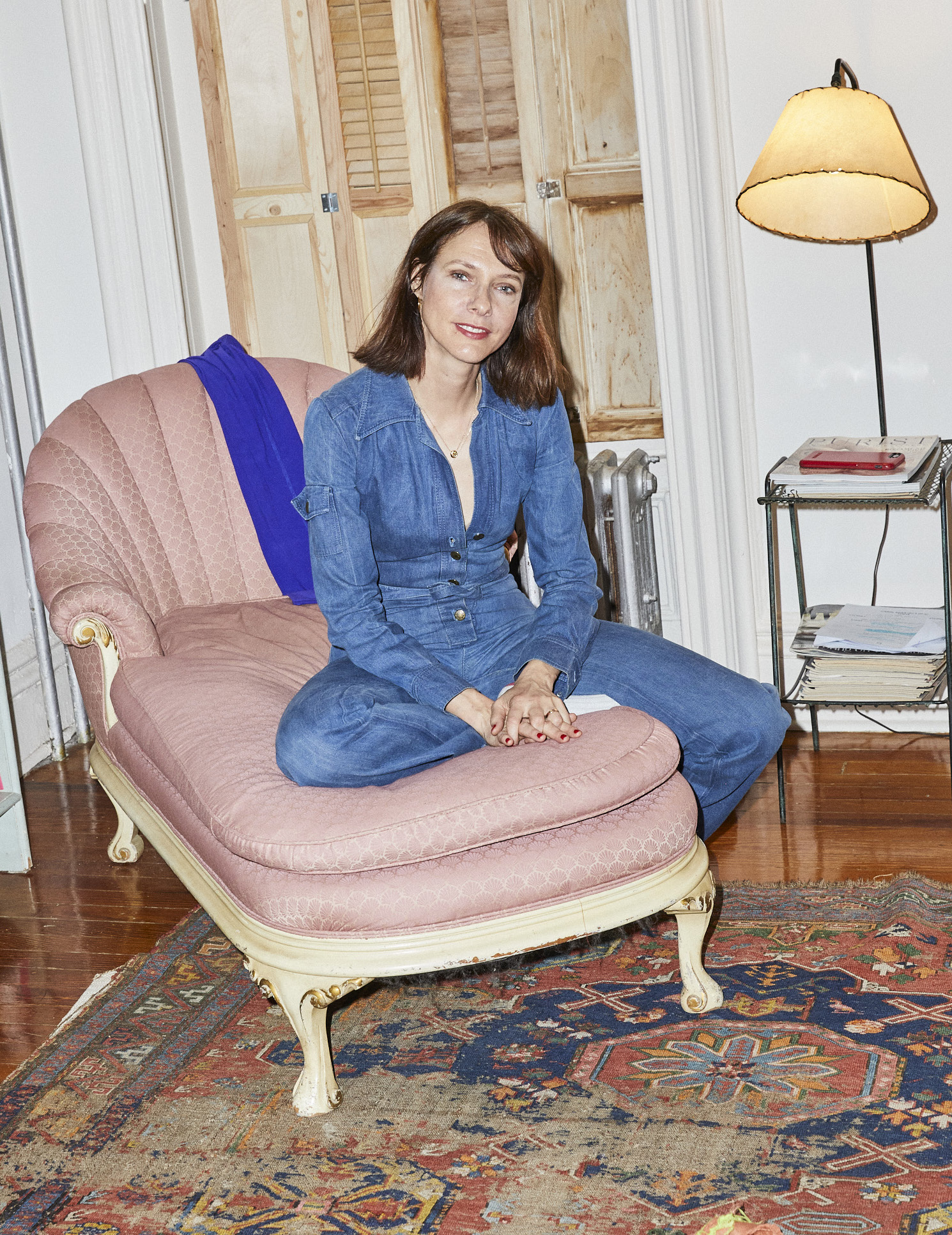 Dolly Wells sitting on a sofa in her apartment