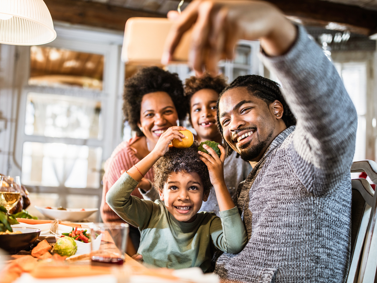 A Black family with two children taking a selfie in their kitchen