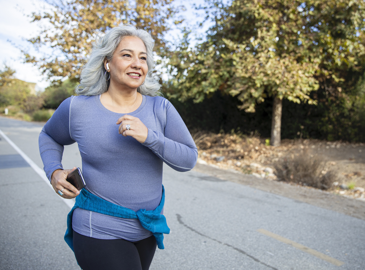 How to start running if you have never ran before: A white-haired woman jogging on a trail
