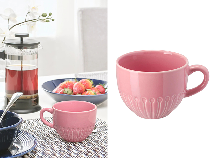 Pink IKEA mug on the kitchen table beside a bowl of berries
