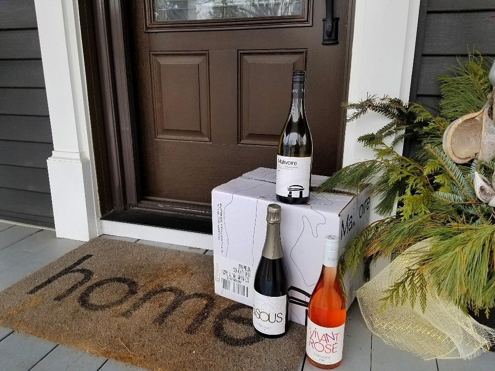 Three bottles of wine with a delivery box on a porch to illustrate a piece on contactless wine delivery in Ontario, BC and Canada