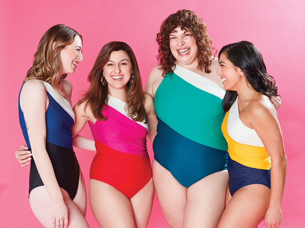 A group of women wearing the Summersalt one-piece Sidestroke swimsuit in various colour against a pink background.