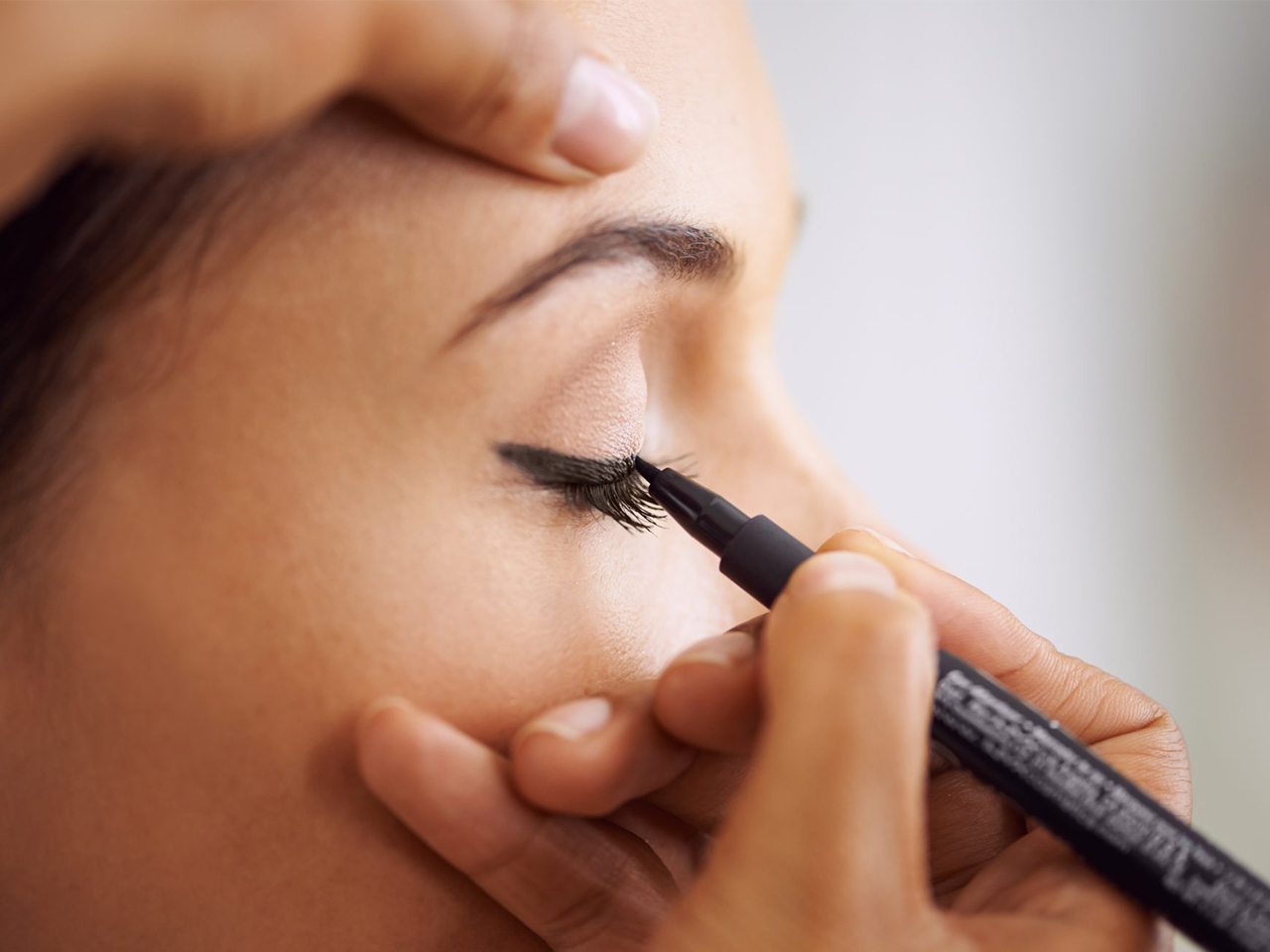 A woman applies liquid eyeliner to an eyelid for a piece on how to apply liquid eyeliner.