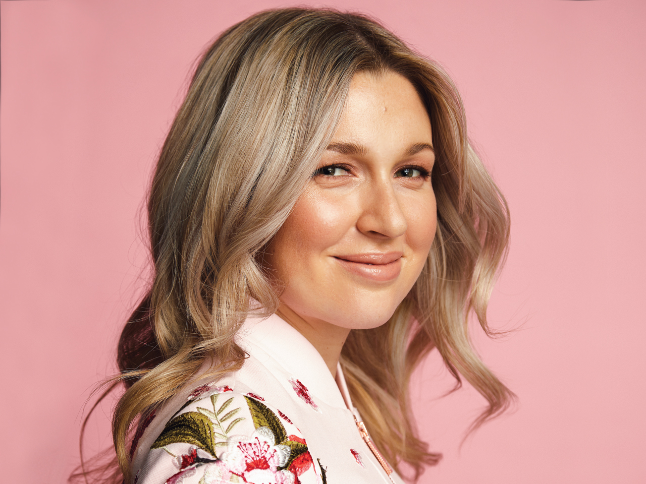 A woman with blonde, voluminous curls on a pink background to illustrate an article on volumizing hair tips for fine hair.