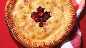 Sour cherry pie with maple leaf cut out, on a red background.