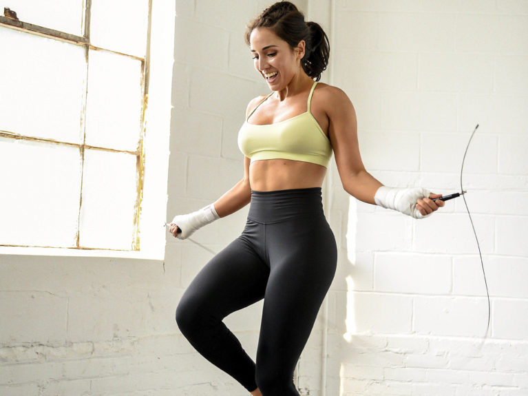 woman in black tights and yellow exercise top jumps rope in a white room
