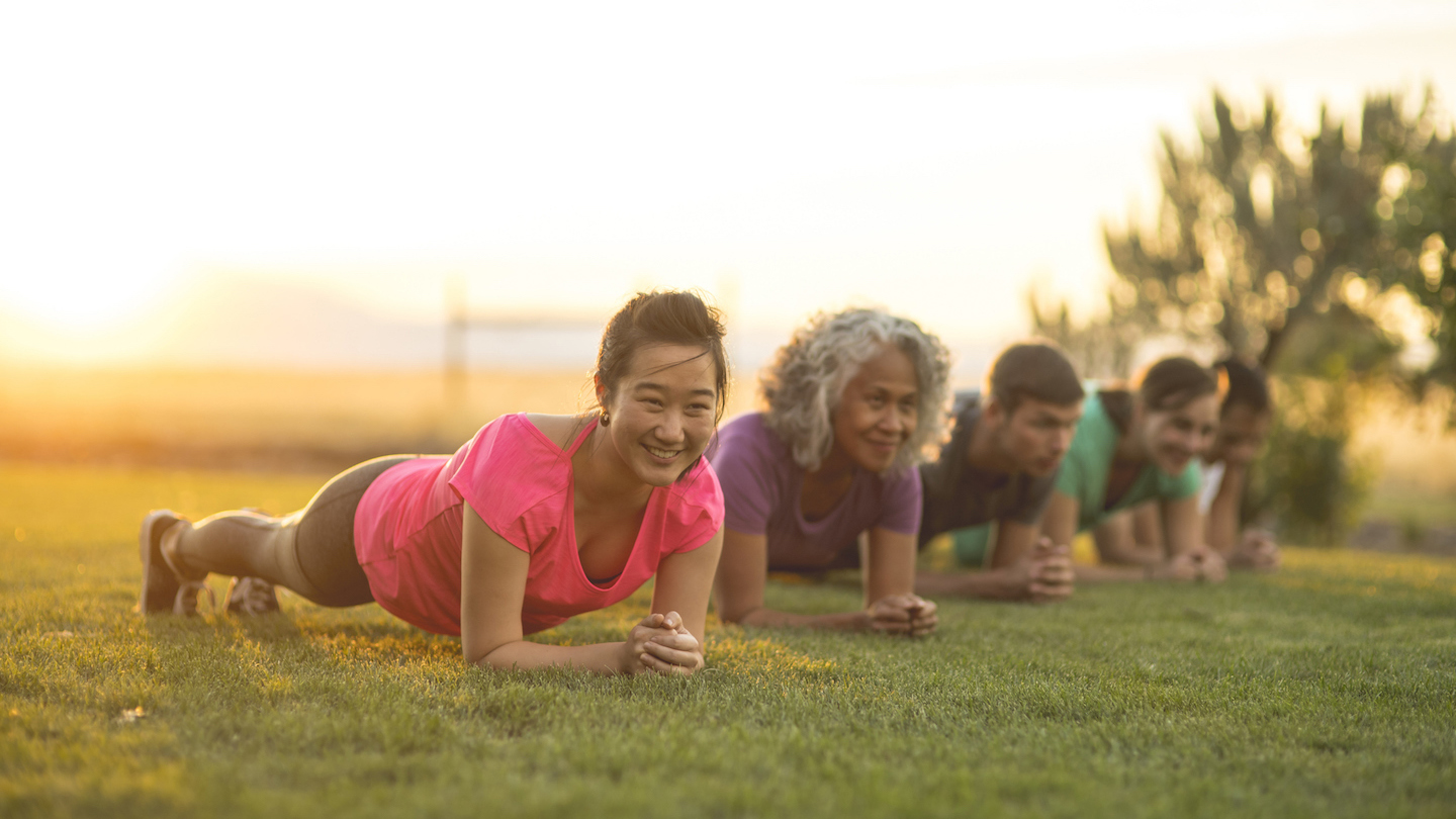 A group of adults attending a fitness class outdoors hold a plank position.