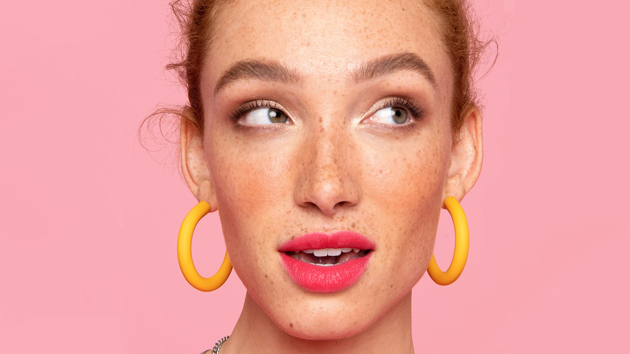 A woman wearing bright pink lipstick and yellow earrings against a pink background for a post on eyebrow makeup products.