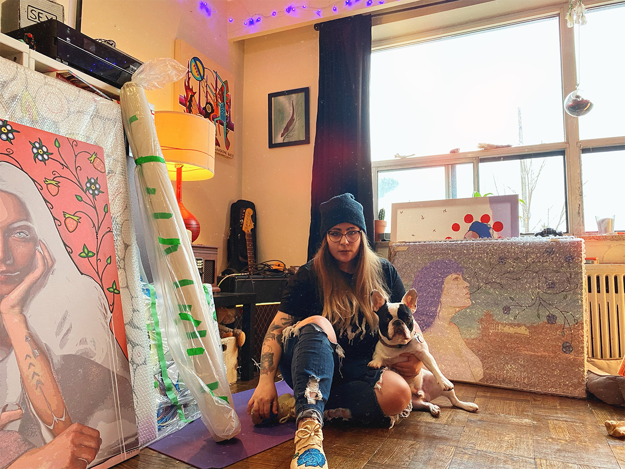 Canadian artist Chief Lady Bird sitting in front of several of her pieces for an article on female artists in Canada.