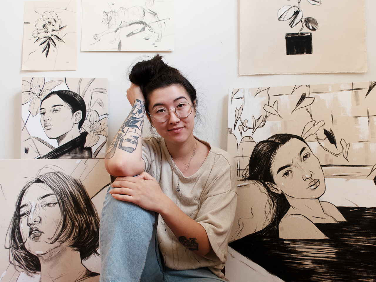 Canadian artist Katie So sitting in front of several of her paintings to illustrate an article on female artists in Canada.