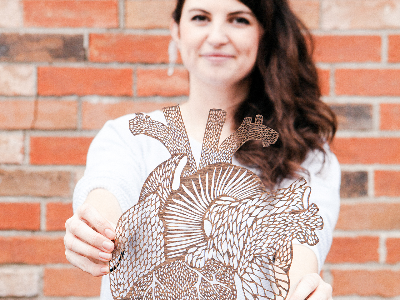Canadian artist and founder of Light + Paper showcasing one of her pieces to illustrate an article on female artists in Canada.