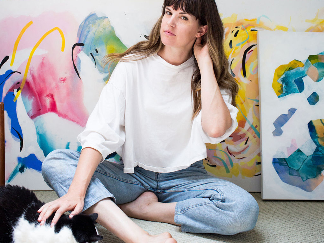 Canadian artist Rachel Hawkes Cameron sitting in front of several large-scale painting to illustrate an article on female artists in Canada.